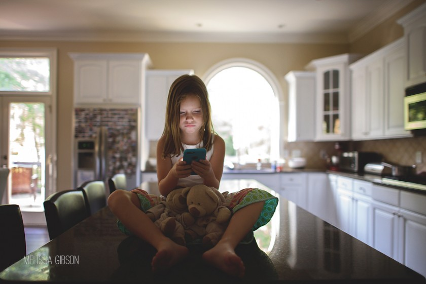 girl sitting on the counter playing on iPhone by Melissa Gibson
