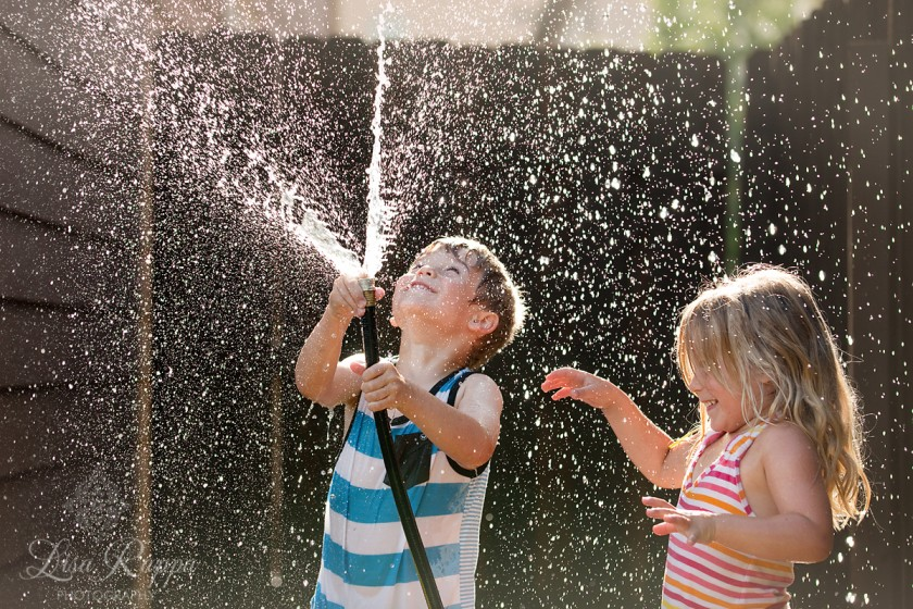 kids playing with a water hose by Lisa Rappa