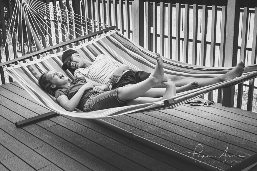 sisters laying in a hammock and laughing by Piper Anne Photography
