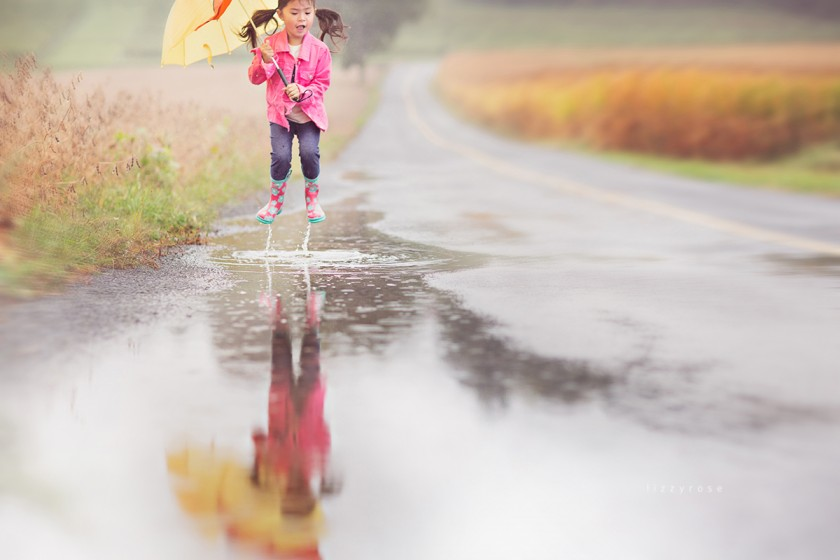 young girl jumping in a water puddle by Lisa Furey