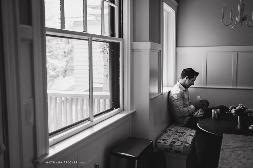 black and white photo of dad feeding newborn by Beth Ann Fricker