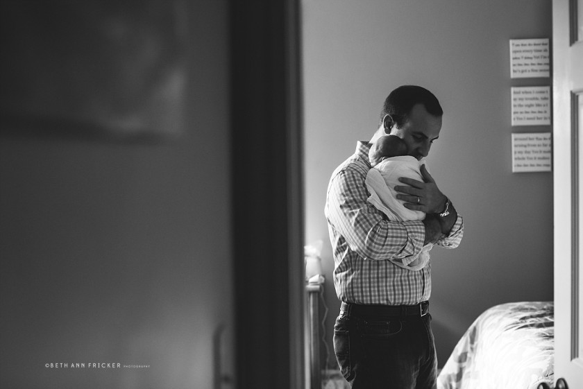 black and white photo of dad holding swaddled newborn by Beth Ann Fricker