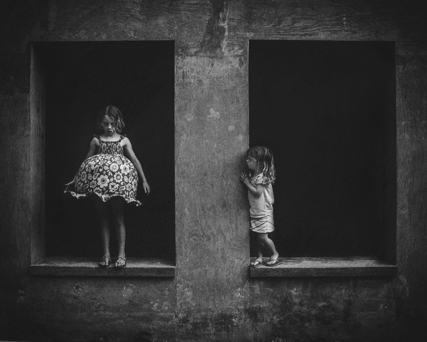 black and white photo of kids standing in windows by Kate T Parker