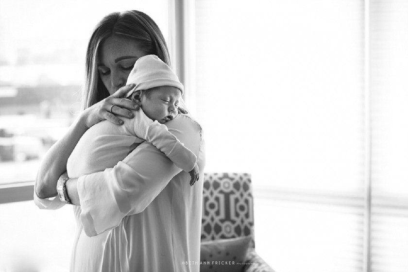 black and white portrait of mom holding newborn by Beth Ann Fricker