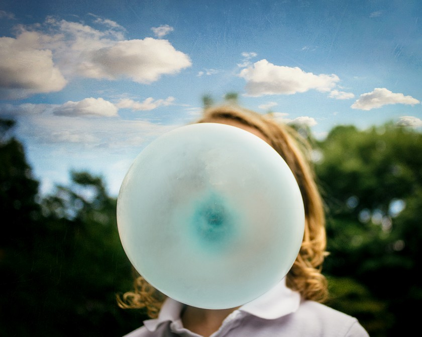 girl blowing a blue bubble by Kate T Parker