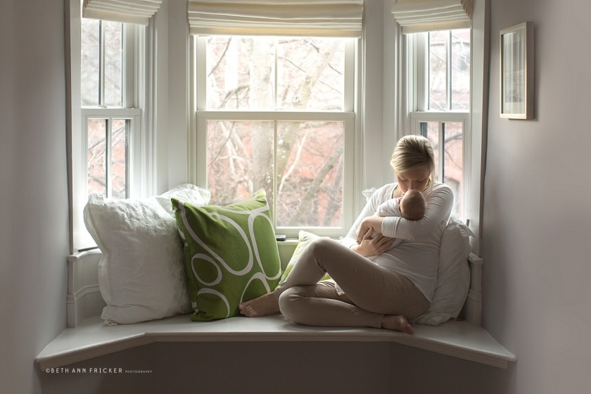 mom sitting in a bay window holding baby by Beth Ann Fricker