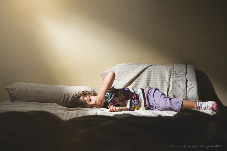 Child-Looking-at-Camera-while-Laying-in-Pretty-Patch-of-Light-by-Carolina-Guerrero