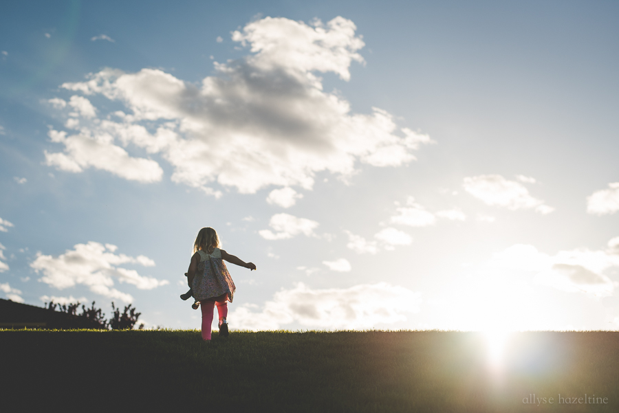 Child-Playing-Outdoors-During-Golden-Hour-In-Beautiful-Light-by-Allyse-Hazeltine