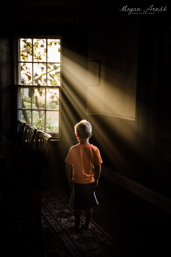 Incredible-Sunbeams-through-Dining-Room-Window-and-Boy-in-Orange-Shirt-by-Megan-Arndt