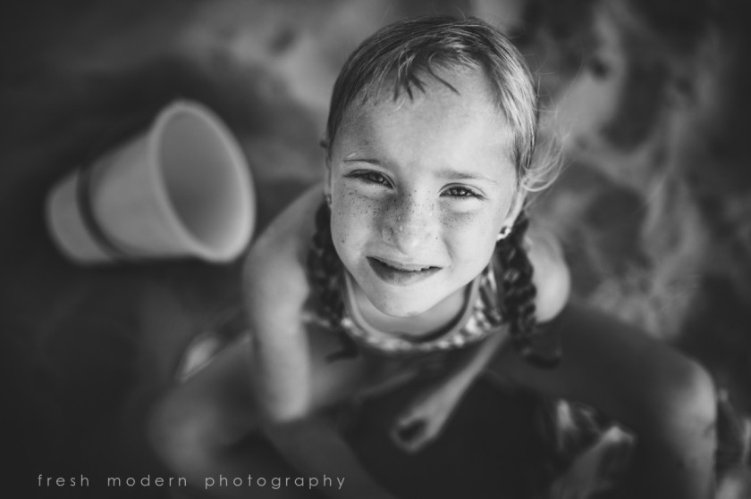 black and white photo of girl playing in the sand by Mickie DeVries of Fresh Modern Photography