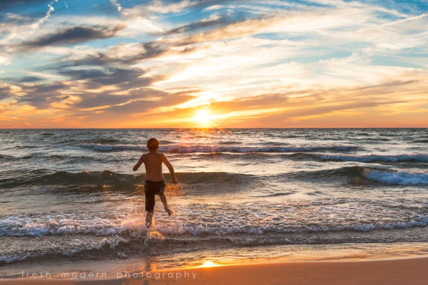 boy jumping in the water at the lake by Mickie DeVries of Fresh Modern Photography