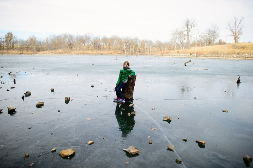 boy standing on a frozen lake by Jenny Solar
