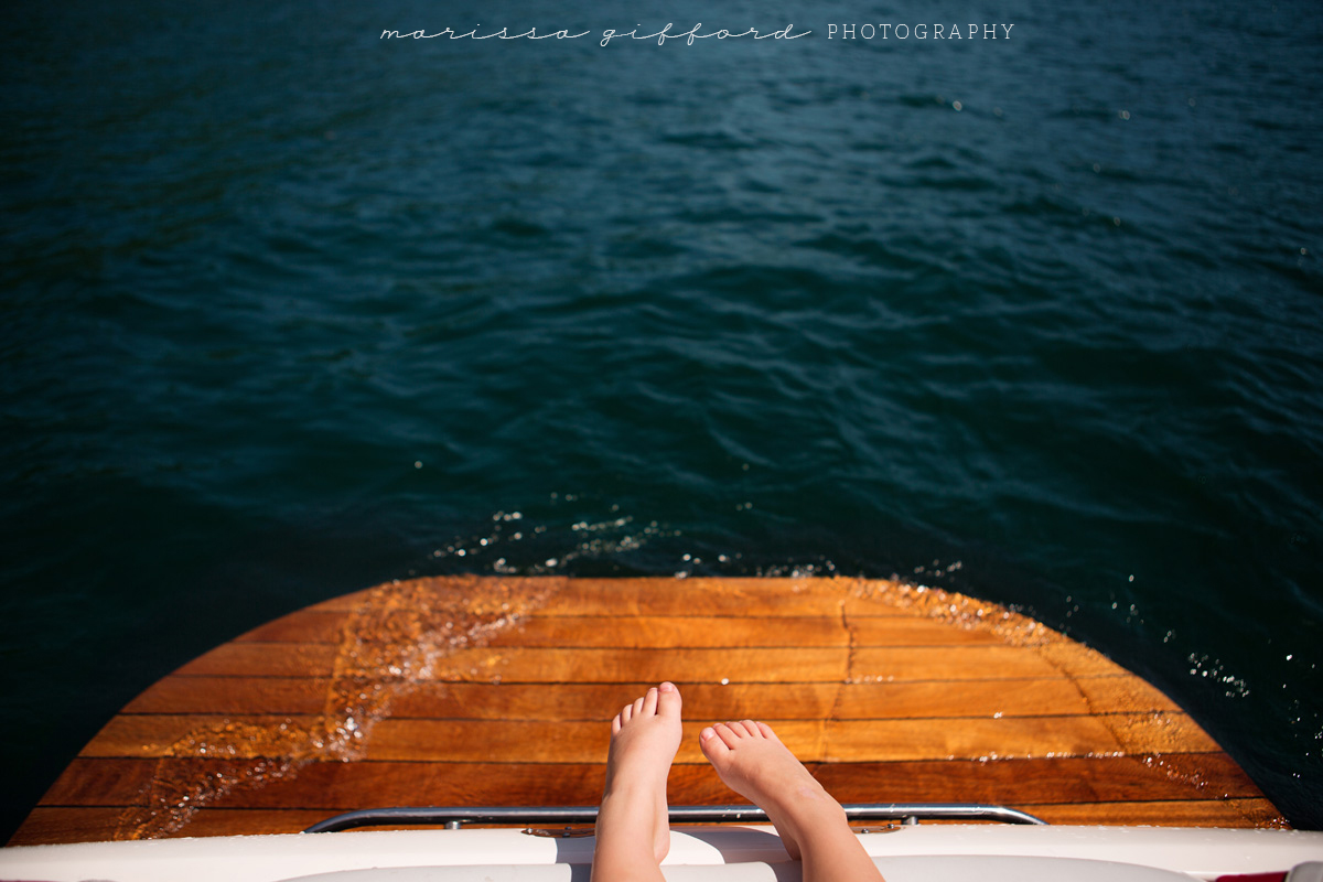 boys feet on a boat by Marissa Gifford