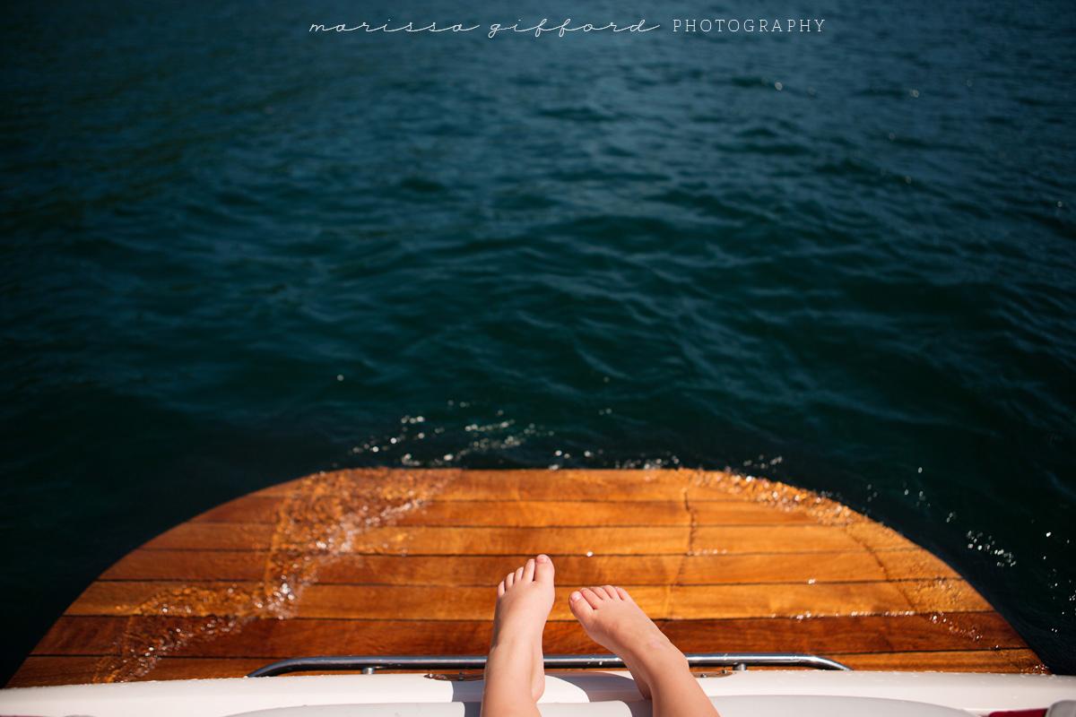 boys feet on a boat by Marissa Gifford