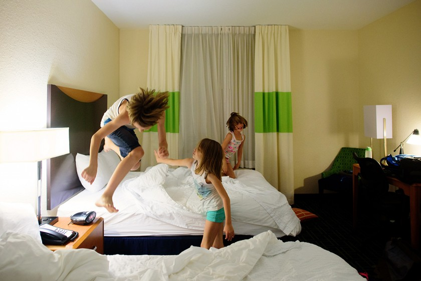 brother and sisters jumping on the bed by Jenny Solar