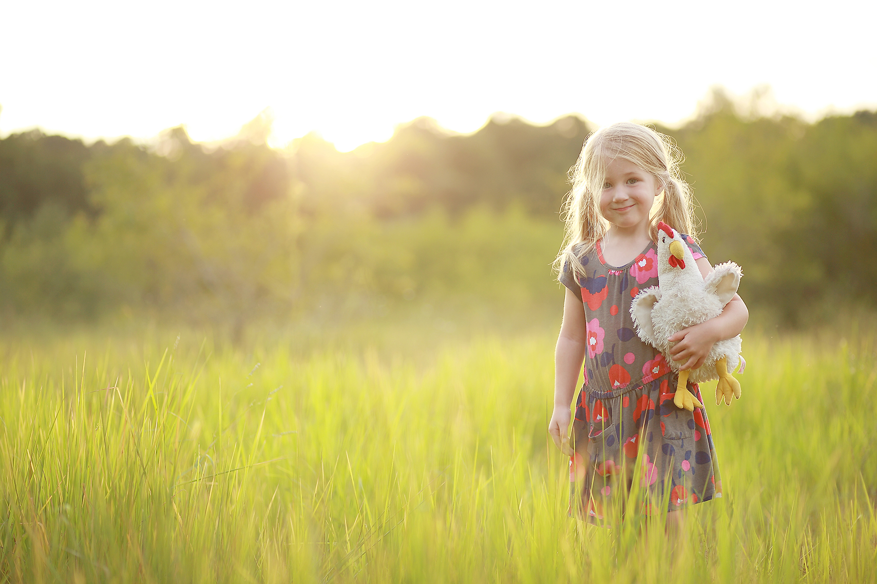 girl holding a stuffed chicken toy by Liz Behm
