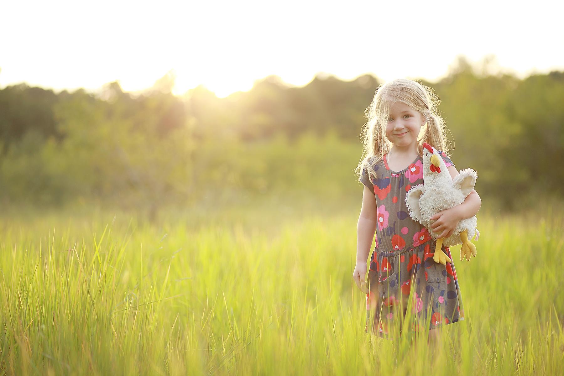 girl holding a stuffed chicken toy by Liz Behm
