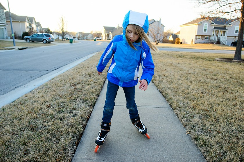 girl rollerblading on the sidewalk by Jenny Solar