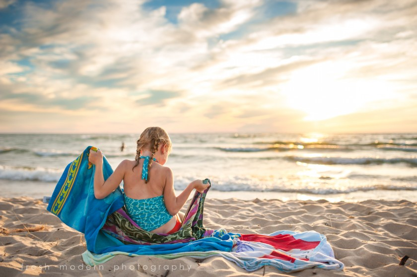 girl sitting on towels at the beach by Mickie DeVries of Fresh Modern Photography