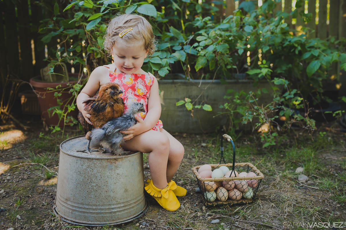 girl sitting with chickens by Sarah Vasquez
