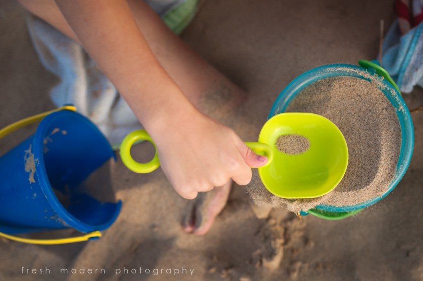 kid scooping sand into a bucket by Mickie DeVries of Fresh Modern Photography