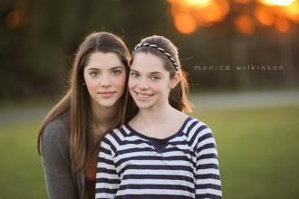 portrait of two sisters in a field by Monica Wilkinson