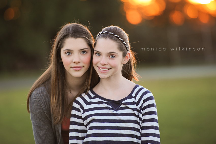 portrait of two sisters in a field by Monica Wilkinson