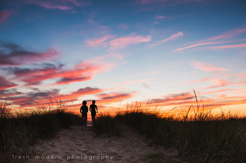 silhouette photo of siblings at the beach by Mickie DeVries of Fresh Modern Photography