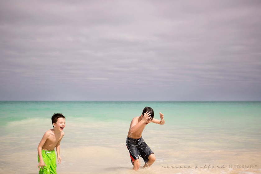 two boys playing in the water by Marissa Gifford