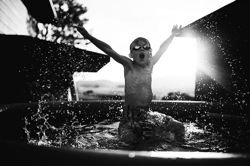 backlit photo of a boy jumping out of the pool by Erin Hensley