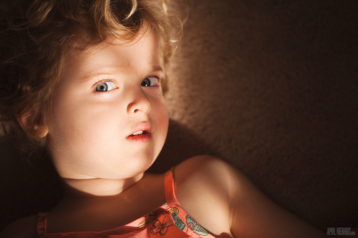 child laying in dappled light photo by April Nienhuis