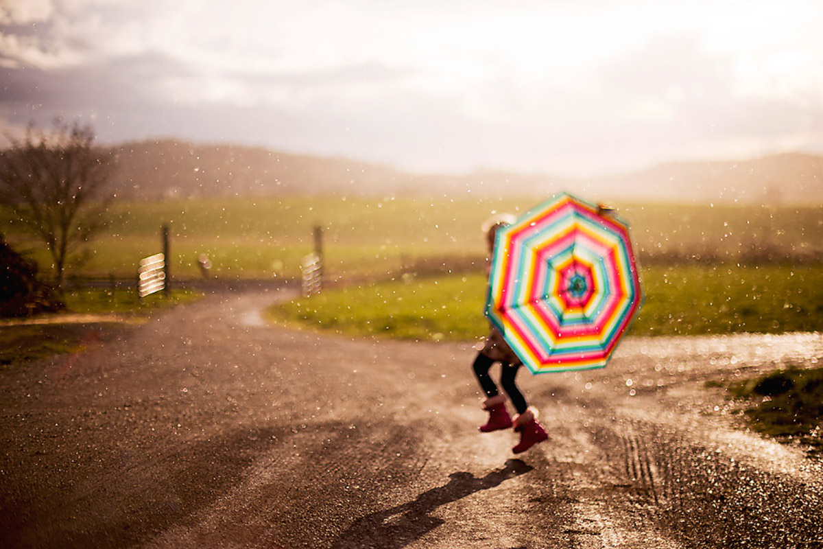child running in the rain with an umbrella by Erin Hensley