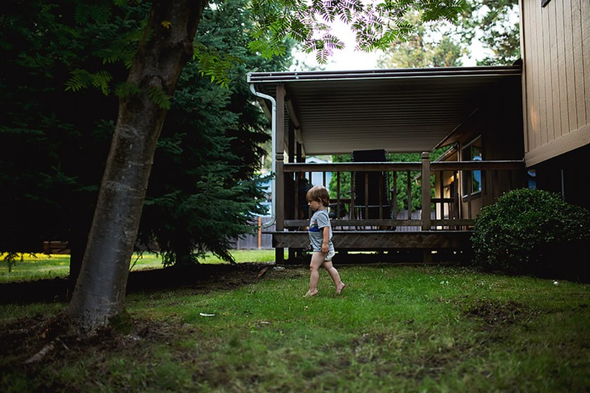 child walking barefoot in the yard by Erin Hensley
