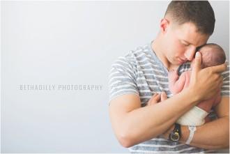 dad holding newborn photo by Beth Deschamp