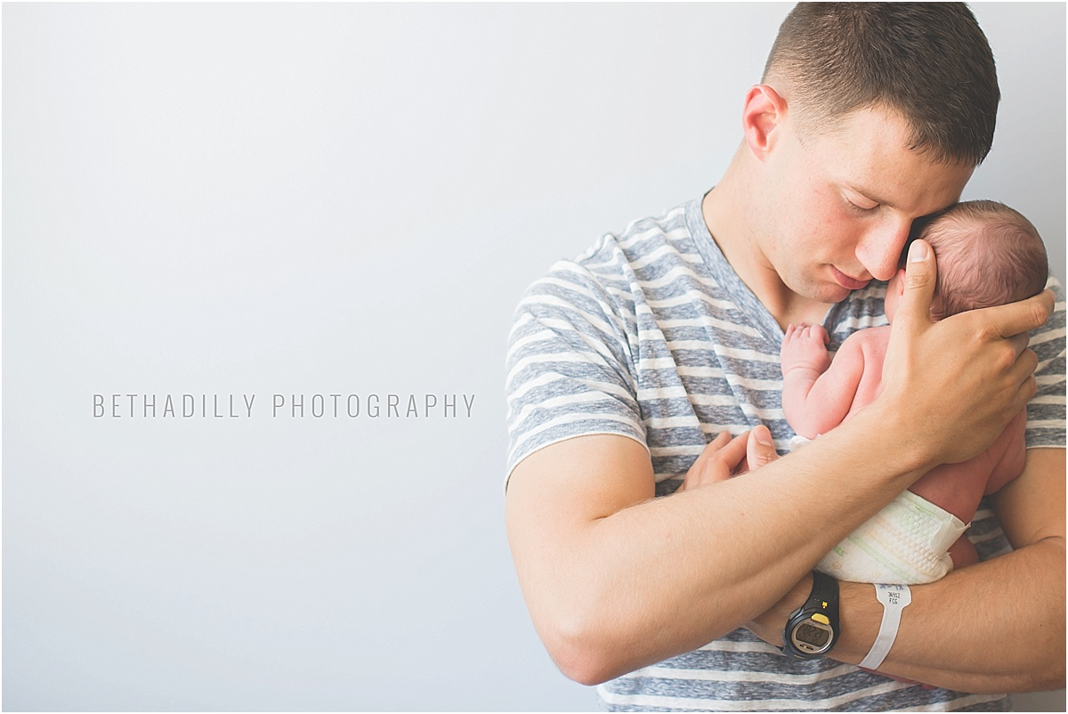 dad holding newborn photo by Beth Deschamp
