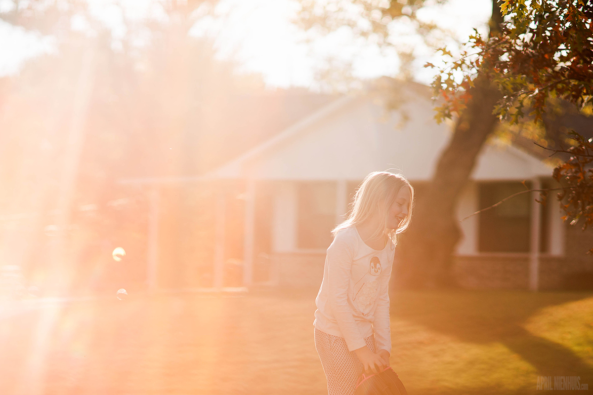 girl laughing with beautiful sunflare by April Nienhuis