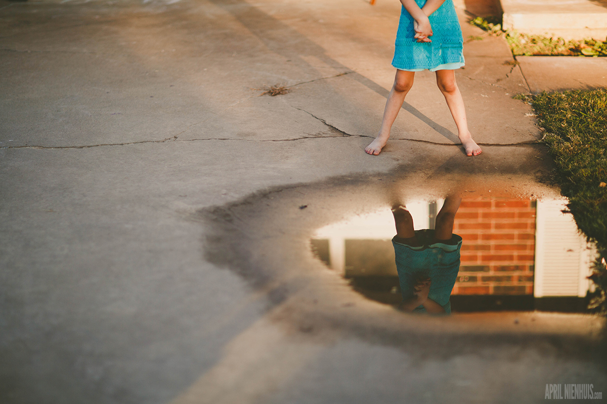 girls reflection in a puddle of water by April Nienhuis