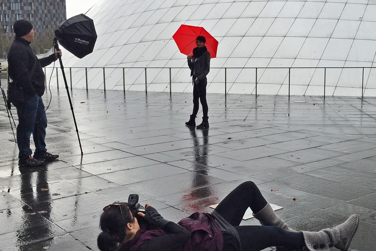 photo of Michelle Turner photographing a woman holding a red umbrella with flash