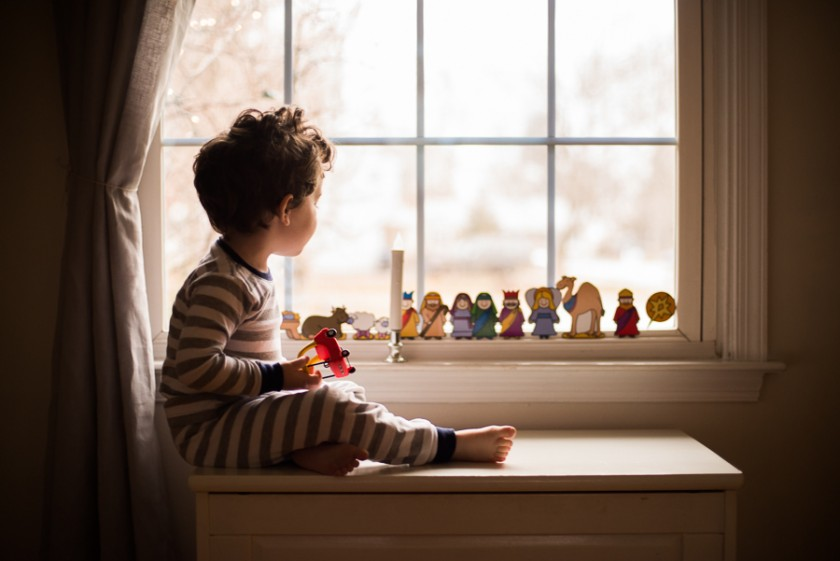boy looking at the holiday decorations in a window by Melissa Stottmann