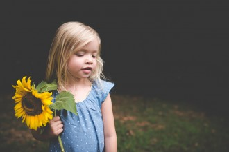 girl holding a large sunflower by Tiffany Kelly