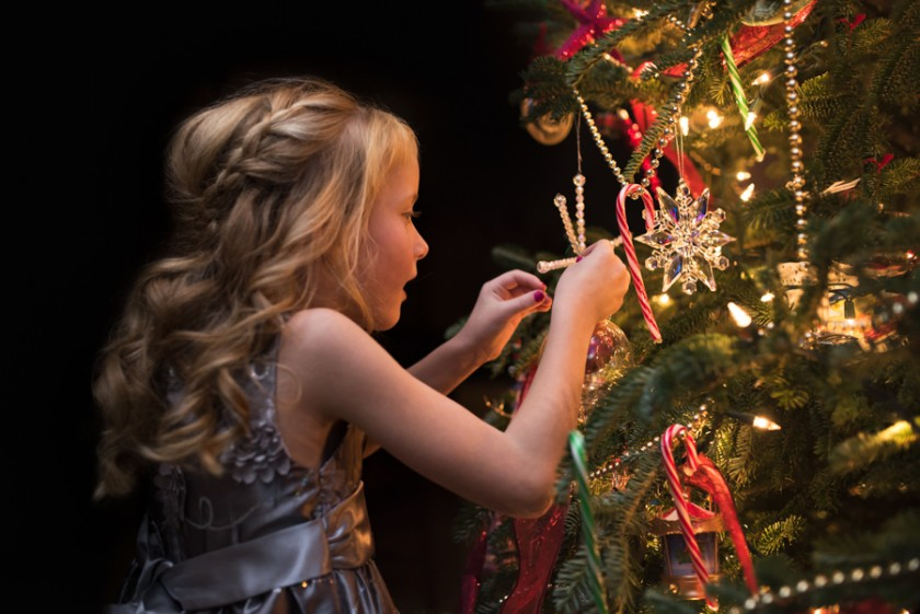 girl putting decorations on the Christmas tree by Mickie DeVries