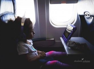 girl watching the ipad on a plane by Elizabeth Ordonez