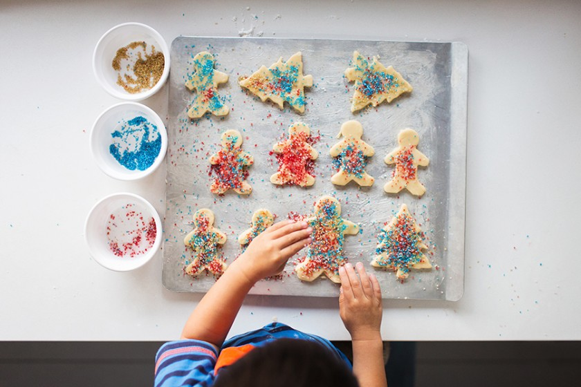 kid decorating Christmas cookies by Vironica Golden