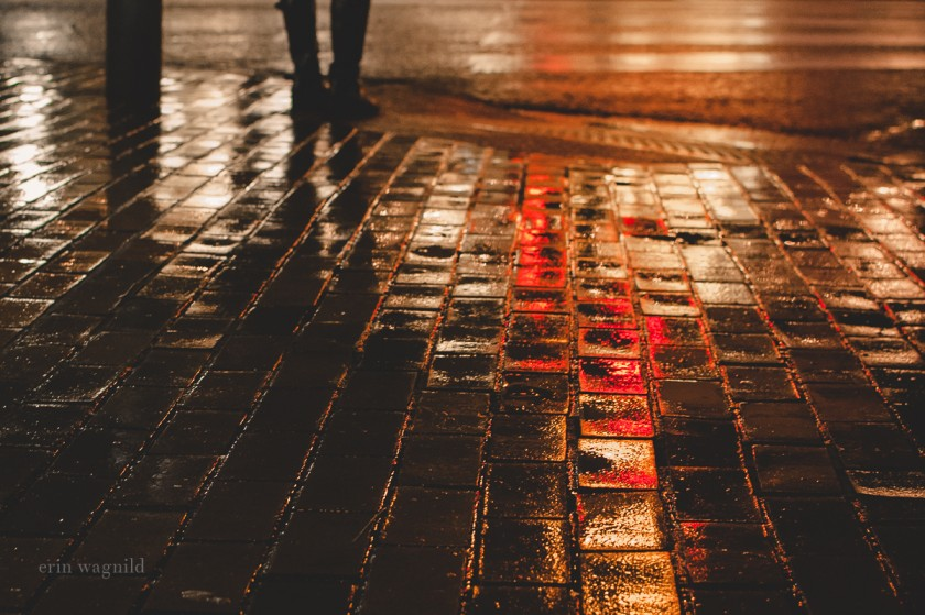 red lights on a wet brick road by Erin Wagnild