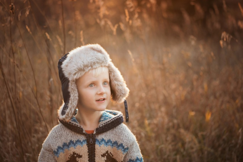 boy with a hat on standing in a field by Megan Loeks