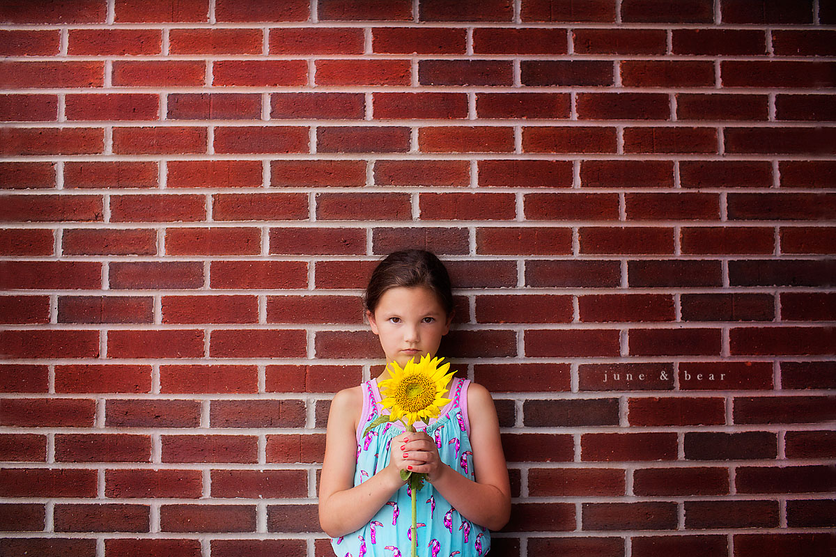 girl holding a sunflower by Kara Orwig of June & Bear Photography