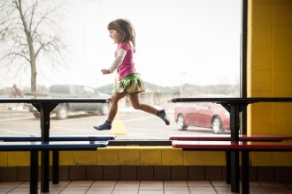 girl jumping across benches by Gretchen Willis