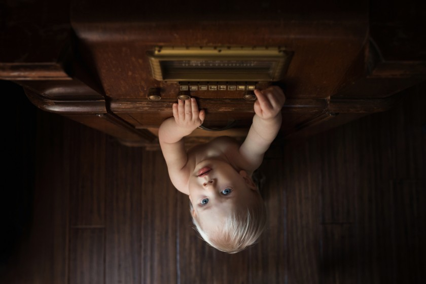 picture of boy playing with antique radio by Megan Loeks