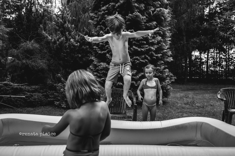 Black-and-White-Documentary-Photo-of-Children-Playing-in-Summer-and-Suspended-Movement-with-Jumping-Child-by-Renata-Plaice