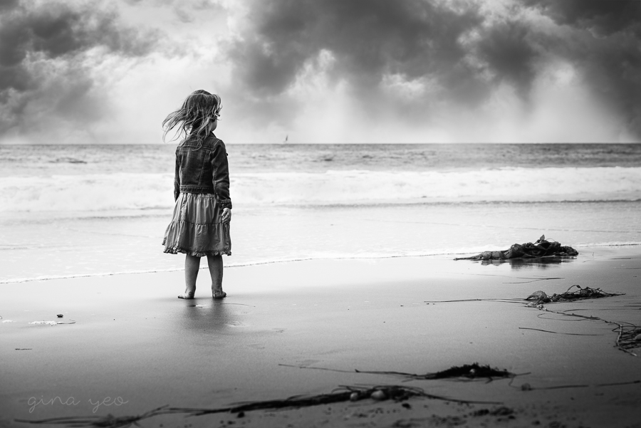 Girl-Standing-on-Beach-with-Wind-Blowing-through-her-Hair-by-Photographer-Gina-Yeo
